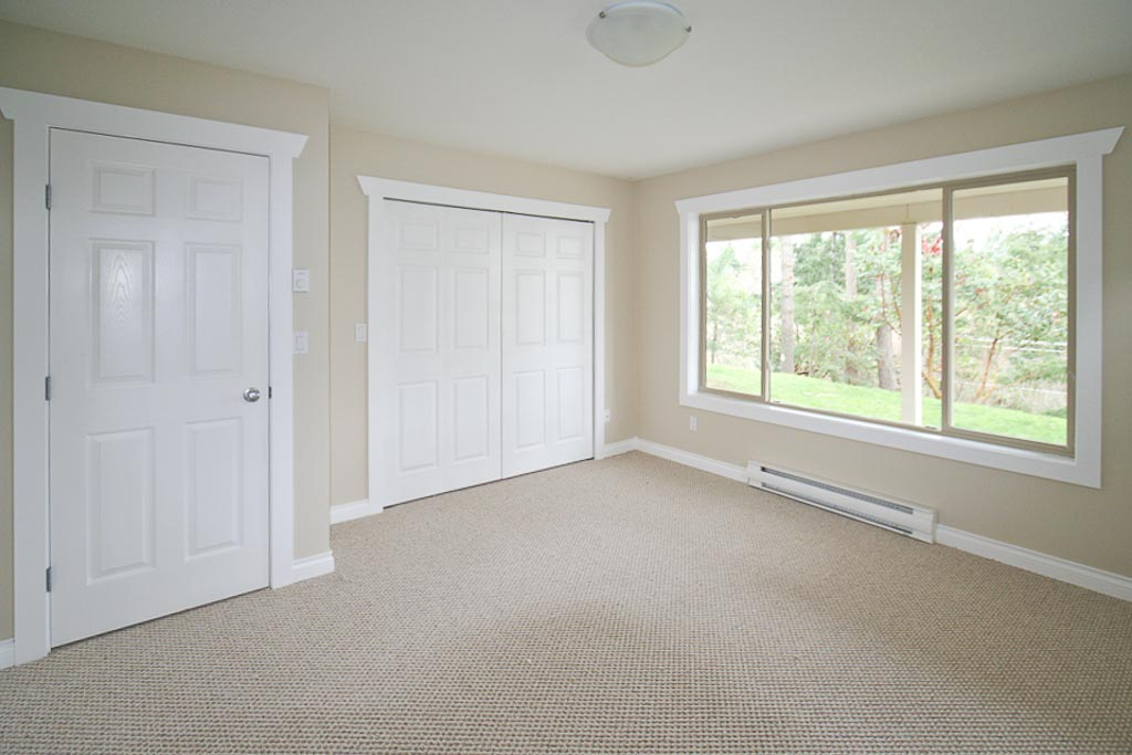 bedroom painted in oatmeal cream colour with white trim and doors