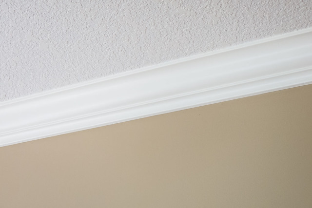 crown molding painted in soft cream colour against brown walls