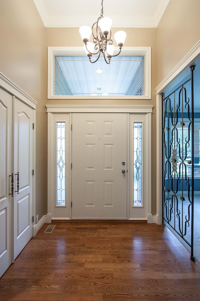 entryway with elaborate trim work painted in neutral beige colour and white trim