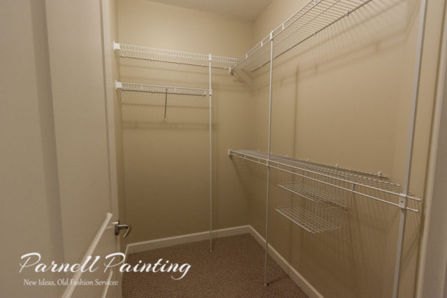 interior of a walk in closet with a shelving system