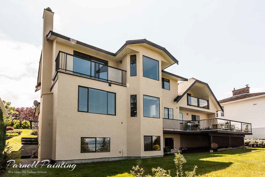 Back of stucco house painted in butter cream with dark - How much to stucco exterior of house ...