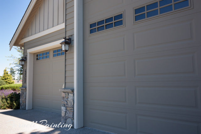 overhead garage doors painted in grey green with light coloured trim